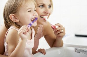 42254340 - mother and daughter brushing teeth together