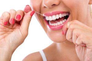 31582004 - dental flush - woman flossing teeth smiling